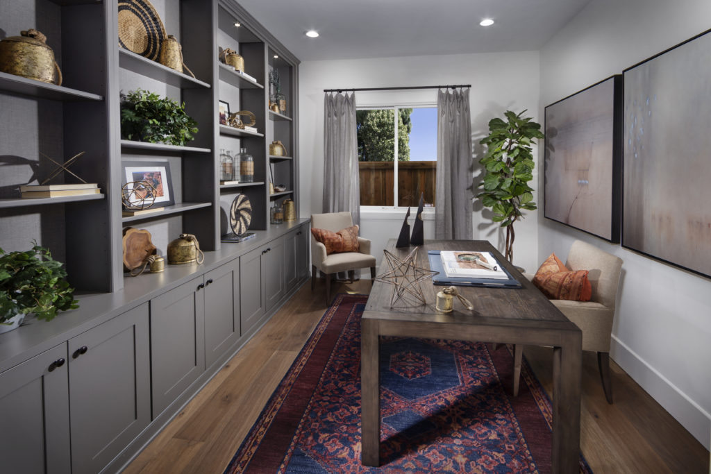 Get home office decor ideas inspired by this office featuring white walls, wood flooring, and a beautiful grey bookshelf.